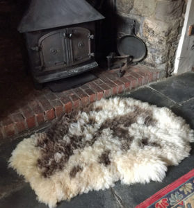 Felted Jacob sheepskin rug next to wood burner